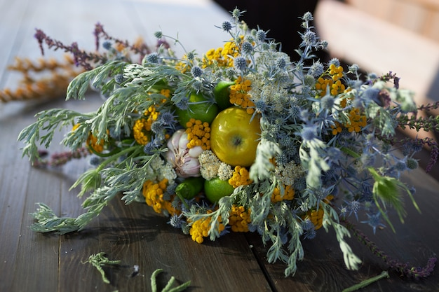 Beautiful fragrant bouquet of wildflowers lie on a wooden table, close-up
