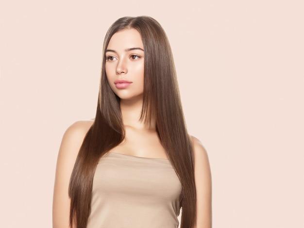 Красивая женщина с веснушками со здоровой кожей и волосами, длинная гладкая концепция прически брюнетки на бежевом