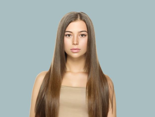 Красивая женщина с веснушками со здоровой кожей и волосами, длинная гладкая концепция прически брюнетки на сером