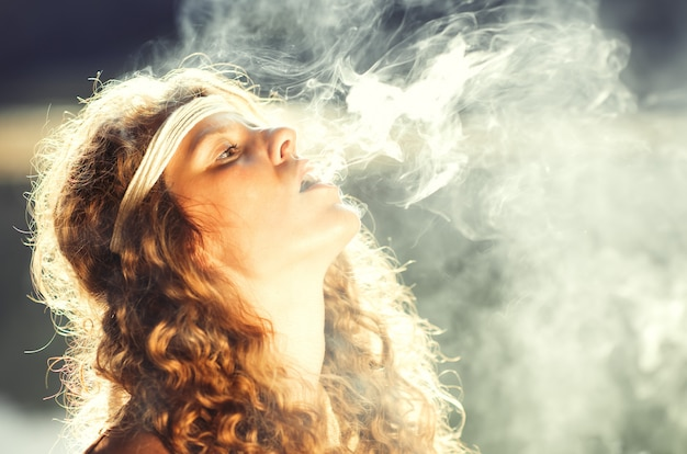 Beautiful free hippie girl blowing smoke