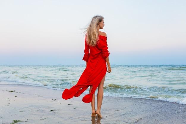 Beautiful free woman in red dress in wind on sea beach walking
