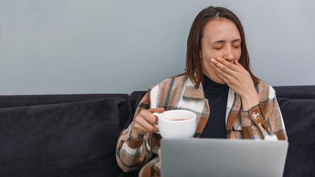Красивая девушка-фрилансер зевает во время работы на ноутбуке