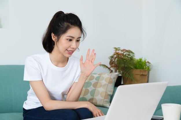 집에서 노트북으로 온라인 화상 회의에서 이야기하는 아름다운 프리랜서 여성