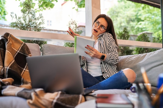 Beautiful freelancer woman work at home and speaking mobile phone.