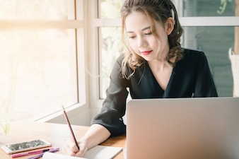 Beautiful Freelancer Woman working online at her home.