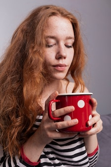 Beautiful frekles woman enjoying cup of coffee
