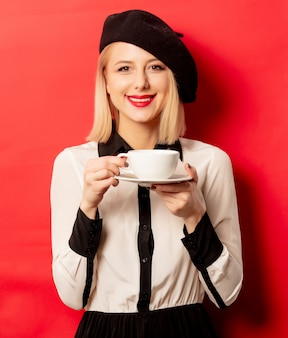 Beautiful french woman in beret holds cup of coffee on red wall