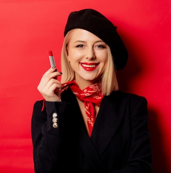 Beautiful french woman in beret with lipstick on red wall