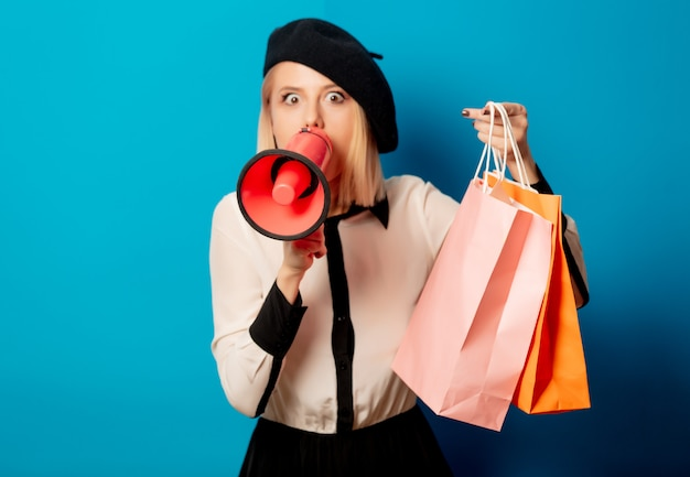 Beautiful french woman in beret with shopping bags and  loudspeaker