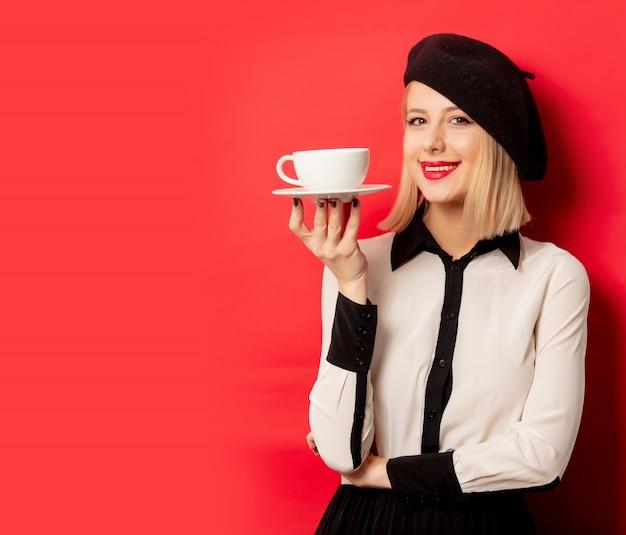 ベレー帽の美しいフランス人女性は赤い壁に一杯のコーヒーを保持します