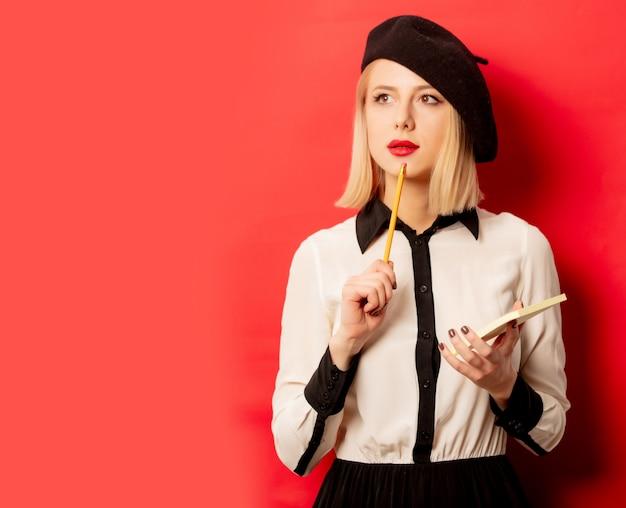 ベレー帽の美しいフランス人女性は赤い壁に鉛筆でノートを保持します