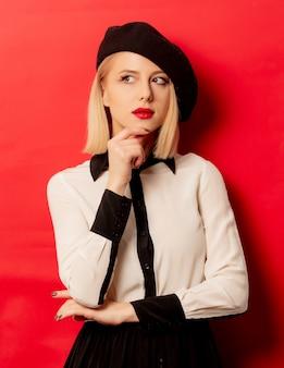 赤い壁のベレー帽で美しいフランス人女性
