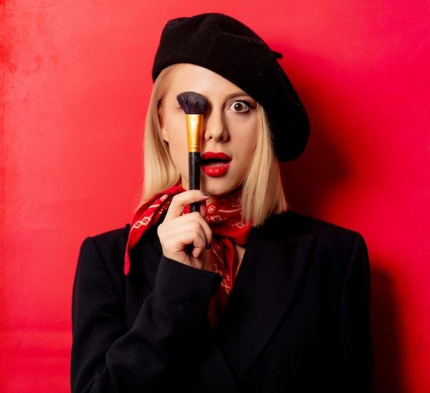 赤い壁に化粧筆でベレー帽で美しいフランス人女性