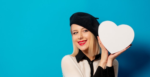 Beautiful frenchwoman in a beret holds a heart-shaped box on a blue wall