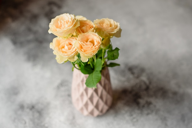 Beautiful fresh beige roses in a clay vase on a concrete background. laying and decoration of a table