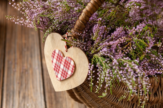 Beautiful fresh bouquet of blooming forest heather in basket and heart symbol