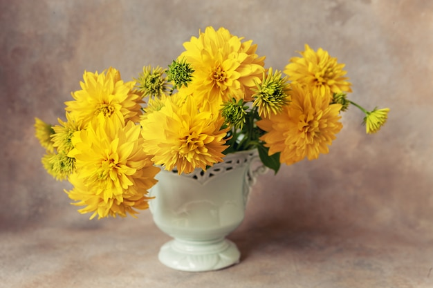 Beautiful fresh bouquet of yellow rudbeckia gold balls in light blue vase.