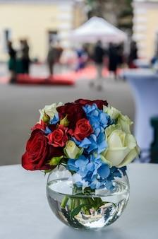 白いテーブルの上のガラスの丸い花瓶に青いアジサイ、赤とクリーム色のバラの美しい新鮮な明るい花束。美しい花の組成物。