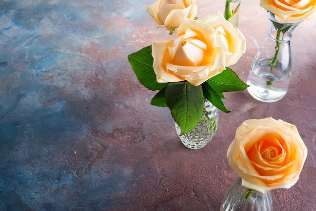 Beautiful fresh cut beige roses in glass vase on stone background.