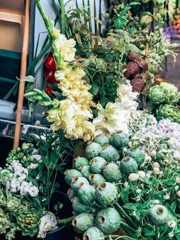 小さな花屋の美しい新鮮な装飾的な巨大なポピーの頭と他の花。ライフスタイルの自然光の構成におけるモダンなスタイルのフラワーアレンジメント。小規模なビジネス。モバイル写真