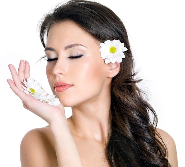 花を持つ若い女性の美しい新鮮な顔-白い背景