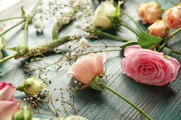 Beautiful fresh flowers on blue wooden background
