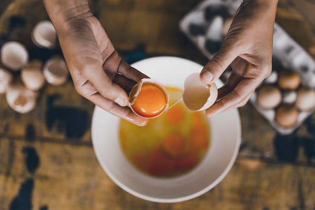 Beautiful and fresh free range egg orange yolk cracked and held with hands
