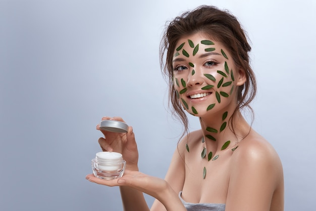 자연스러운 메이크업과 크림을 들고 카메라를 찾고 몸에 녹색 잎을 가진 아름 다운 신선한 소녀