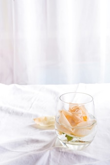 Beautiful fresh head beige roses in glass on light background.