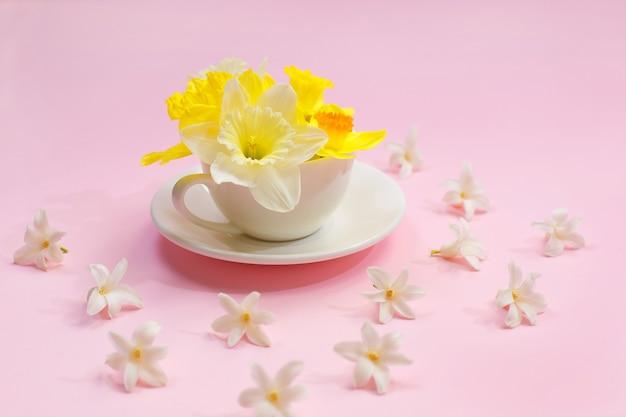 Красивый свежий нарцисс в чашке на розовом столе.