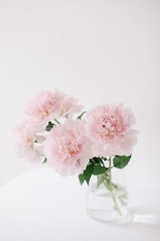 Красивые свежие розовые пионы в вазе в домашнем интерьере