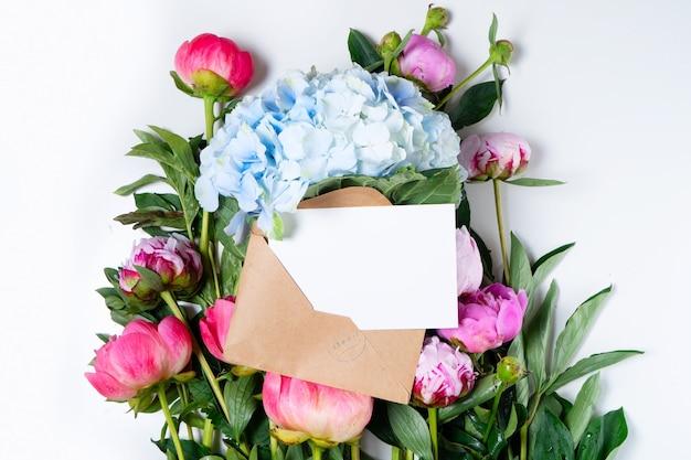 白いテーブルの上の美しい新鮮なピンクの牡丹とアジサイの花のクローズアップ、上面図、白いカードのコピースペースとフラットレイ背景