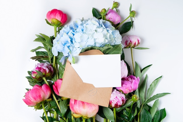 Beautiful fresh pink peony and hydrangea flowers on white table close up, top view and flat lay background with copy space on white card