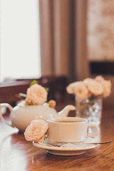 Красивые свежие розы возле чашки чая и романтическое настроение в пастельных тонах.