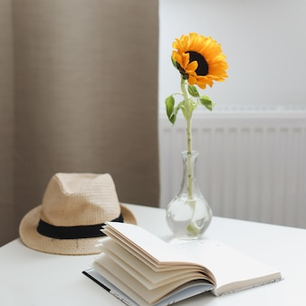 아름 다운 신선한 해바라기 밀짚 모자와 책