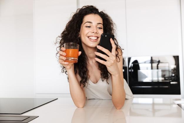 Красивая свежая женщина 20 лет с вьющимися волосами, одетая в шелковую одежду для отдыха, пьет сок на кухне и с улыбкой пользуется черным мобильным телефоном
