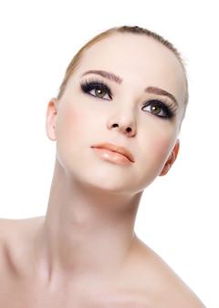 白で隔離される黒のアイメイクで美しい新鮮な女性の顔