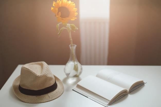 美しい新鮮な黄色のヒマワリ、麦わら帽子、カーテンのある窓際のテーブルの上の本