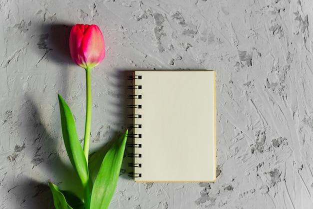 美しい新鮮なピンクのチューリップと灰色のコンクリートテーブルの空の空のスパイラルメモ帳をカット