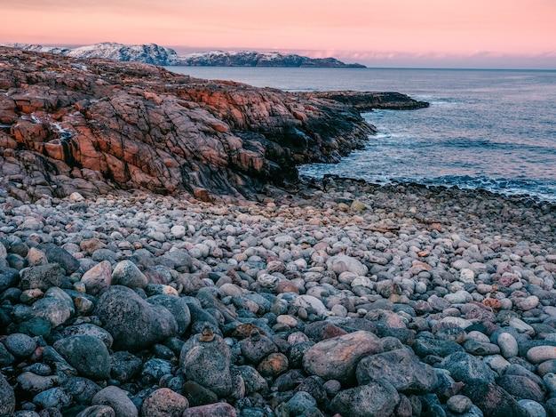 山の岩だらけの斜面にある美しい凍った水たまりと苔。テリベルカの美しい北極の風景。カラフルな山の風景。