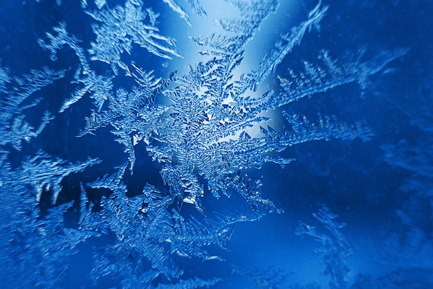 Beautiful frozen snowflakes on glass, macro photo background, winter theme