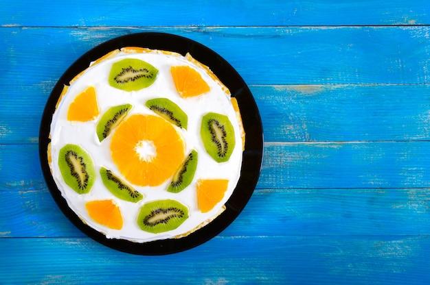 青い木製の背景に美しいフルーツケーキ。オレンジ、キウイのお祝いケーキ。上面図。お誕生日おめでとうございます。