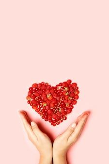 복사 공간와 분홍색 배경에 여성 손으로 열매의 아름 다운 과일 심장에 의하여 이루어져있다. 위에서 봅니다. 세로 사진