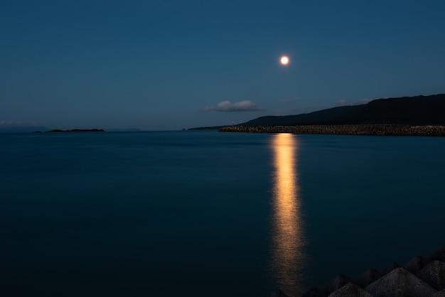 황혼에서 바다에 반영하는 산 뒤에 상승하는 아름 다운 보름달. 이리 오모테 섬.