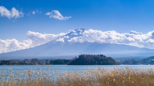 A beautiful full view of the fuji mountain with snow and clouds covering the top.