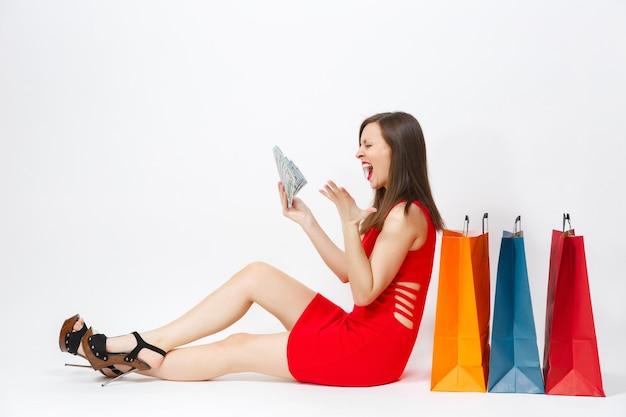 現金ドル、白い背景で隔離の買い物後の購入とマルチカラーパケットで座っている赤いドレスの美しい楽しい魅力ファッショナブルな若い女性。広告用のスペースをコピーします。