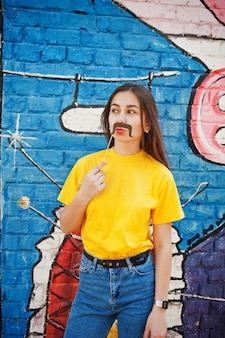 Beautiful fun teenage girl with banana at hand, wear yellow t-shirt, jeans and mustache on stick near graffiti wall.