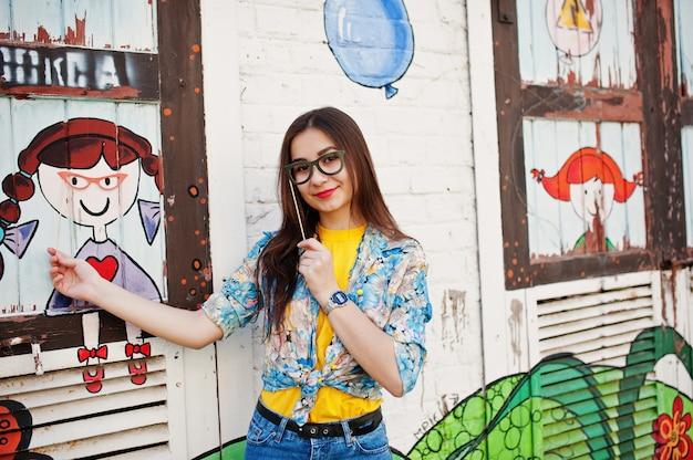 Beautiful fun teenage girl with glasses on stick wear yellow t-shirt, jeans near graffiti wall.