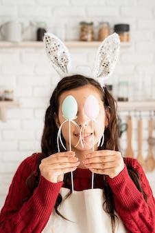 빨간 스웨터와 부활절 달걀 장식으로 눈을 덮고 하얀 앞치마에 아름 다운 재미있는 갈색 머리 여자