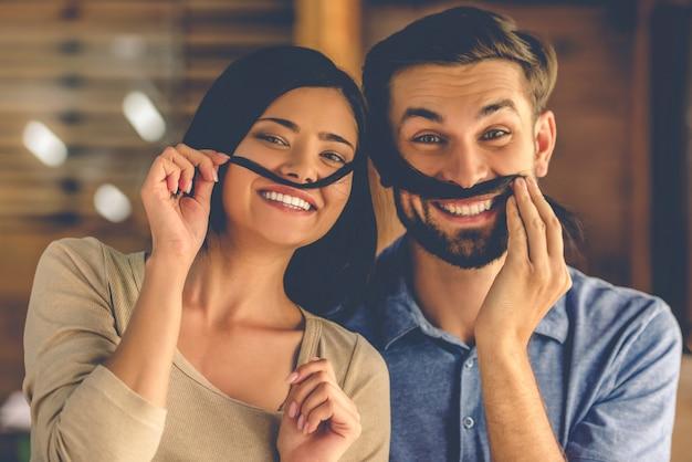 美しい面白いカップルは、女の子の髪の口ひげを作っています。